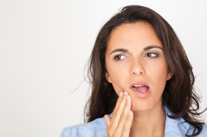 Woman holding her mouth in pain because she needs a tooth extraction.