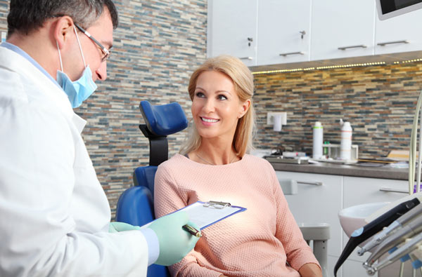 Woman talking to her dentist during a dental exam at Watermark Dentistry in Normandy Park, WA